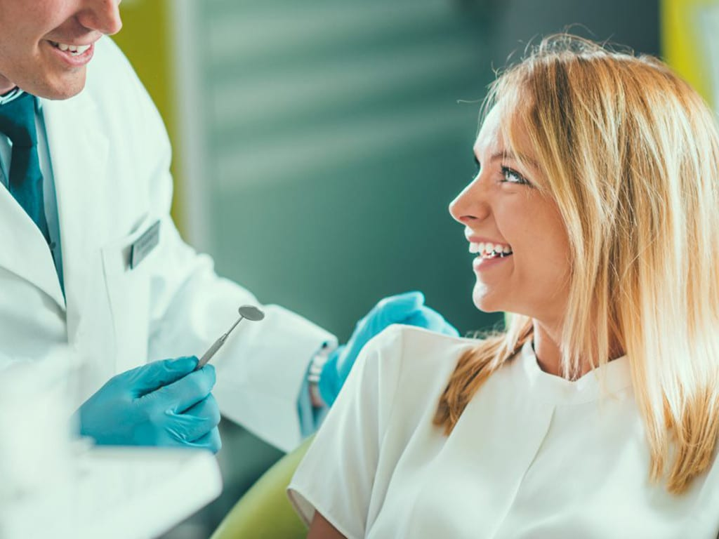 Woman smiling and receiving oral exam by dentist