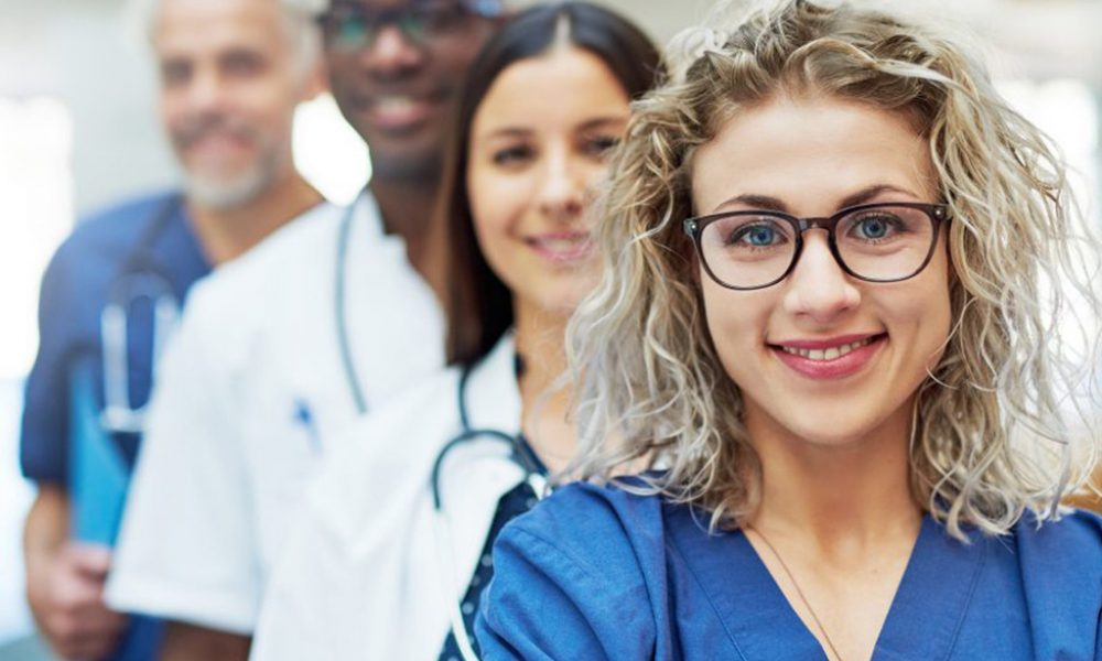 Curly haired blonde girl in glasses wearing blue scrubs with coworkers standing behind her