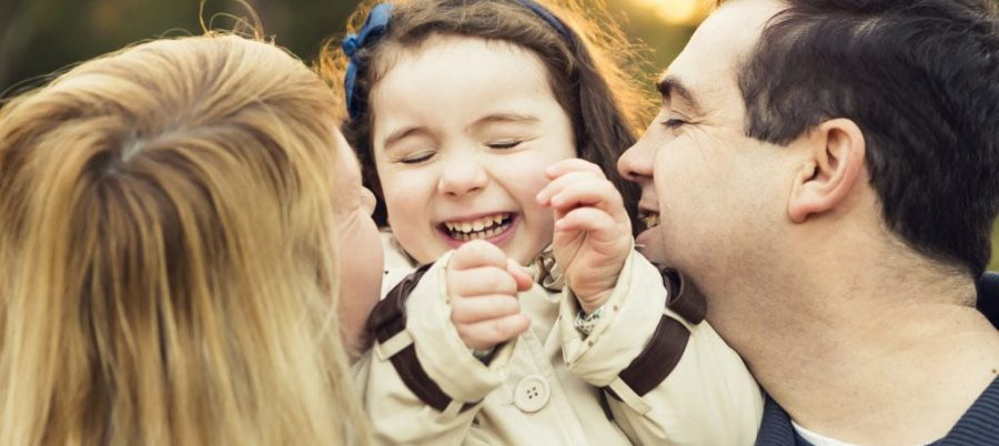 Mom and dad doting on little girl with a sweet smile on her face