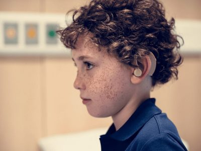 Side profile of brown curly haired kid with hearing aid in left ear
