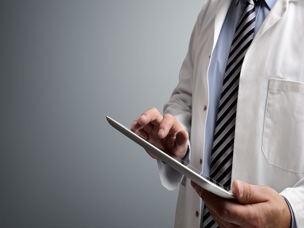 Doctor in lab coat and stripped tie working on tablet