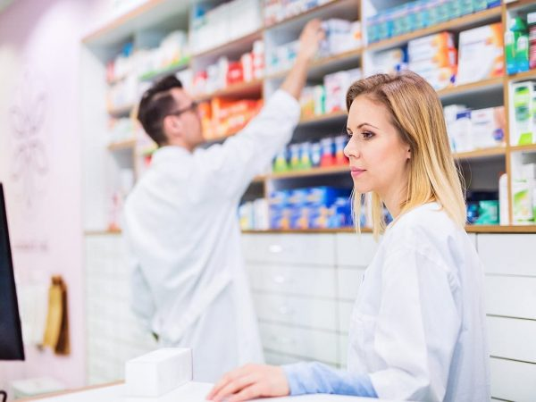 Pharmacist reviewing medications with co-worker in the background