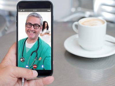 Doctor in green scrubs on smartphone for telemedicine