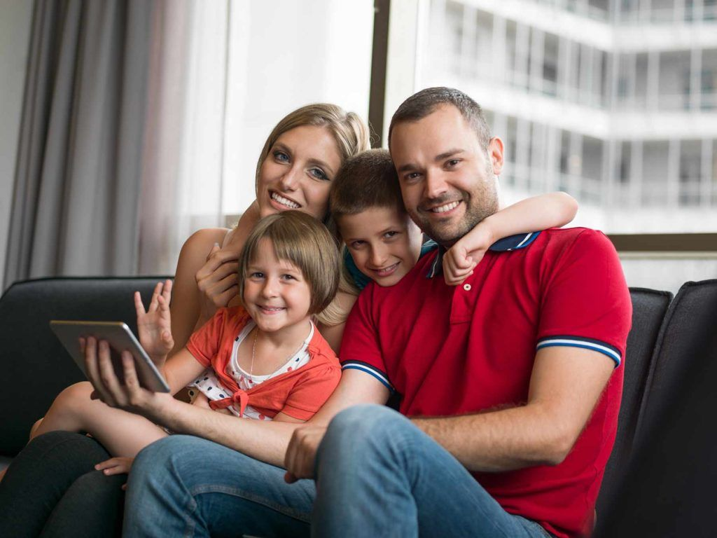 Mom, dad, boy and girl sitting on the couch looking at a tablet