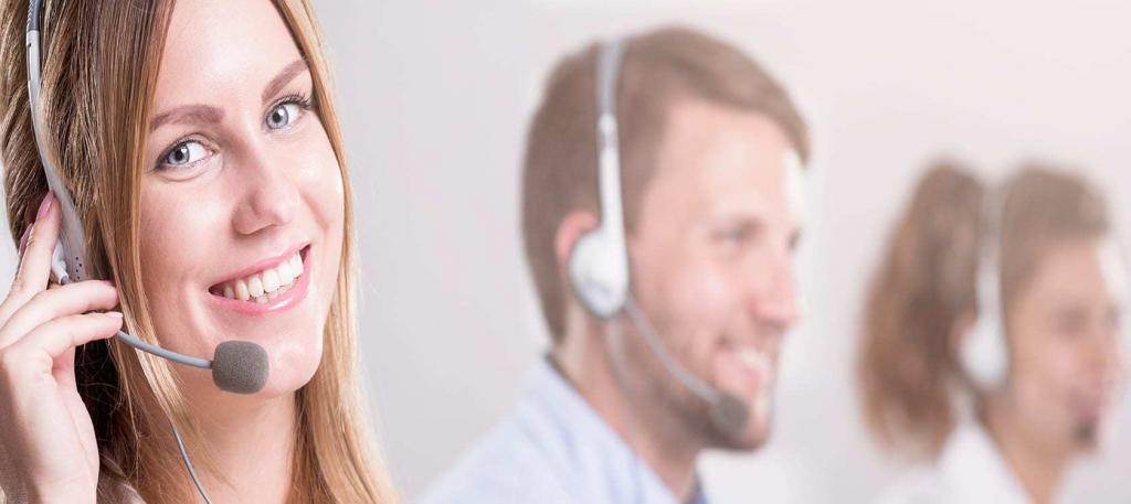 Call center girl smiling at camera with head set in place and guy faded out in the background