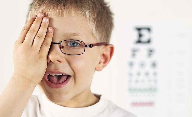 Little blonde haired boy with prescription glasses in place, covering one eye