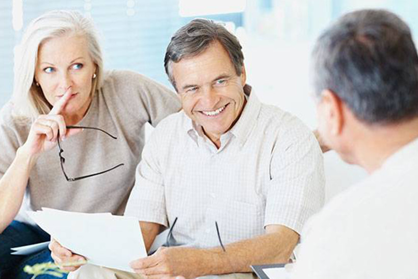 Husband and wide reviewing a term life insurance policy with their broker