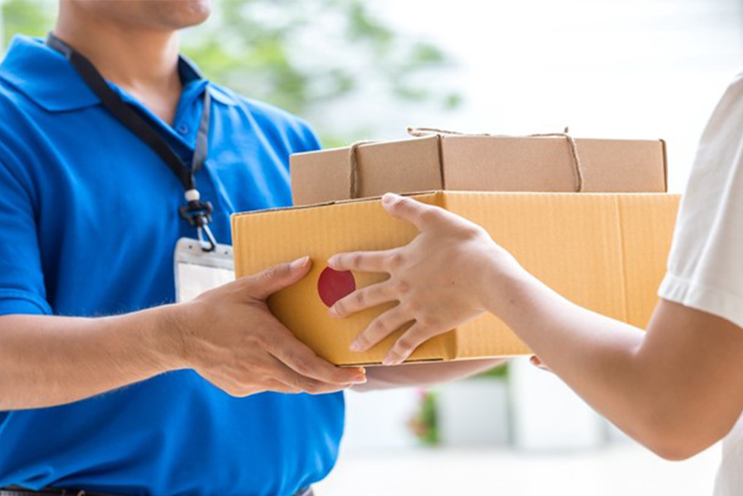 Delivery man in blue shirt handing packages over to a woman in a white shirt