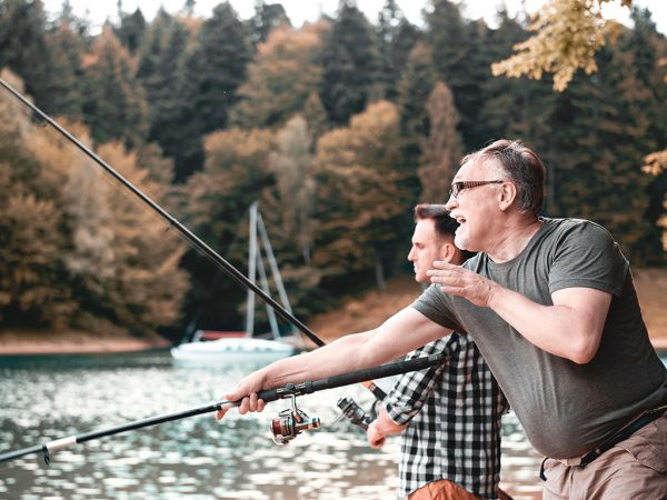 Dad and Son Fishing at the lake with a boat in the background