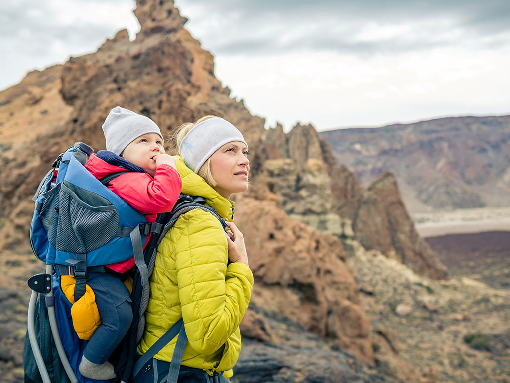 Mom carrying baby on her back in hiking pack walking through the mountains