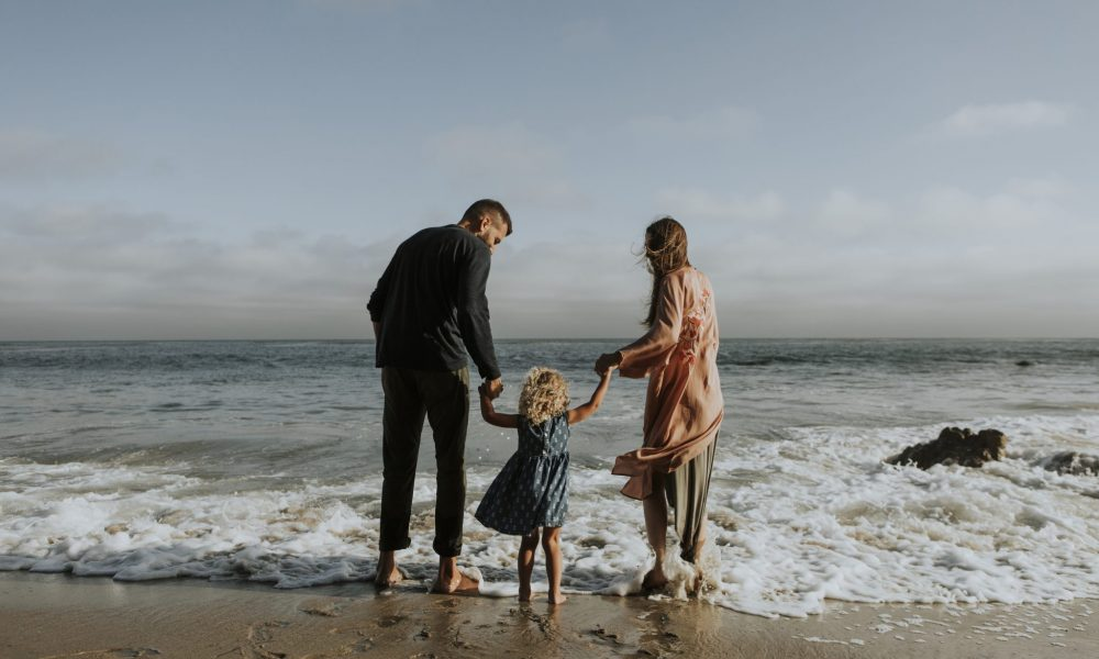 Mom and Dad with little blonde girl standing at the beach putting their feet in the water