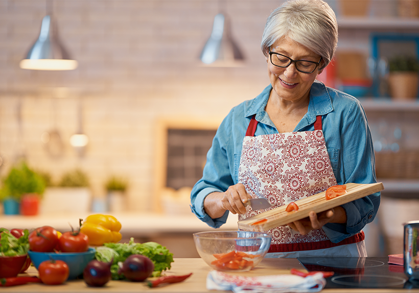 Older woman standing in the kitchen prepping vegetables with a knife, cutting board and bowl