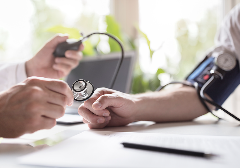 doctor checking blood pressure with an arm cuff and stethoscope
