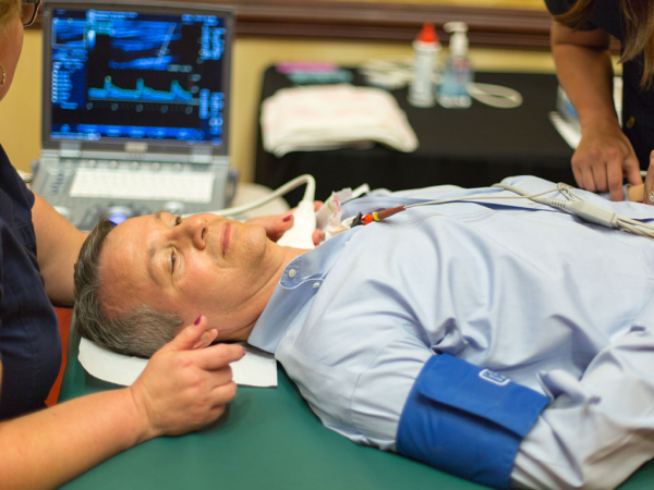 Man laying on a medical table receiving a carotid artery preventative health screening check via ultrasound
