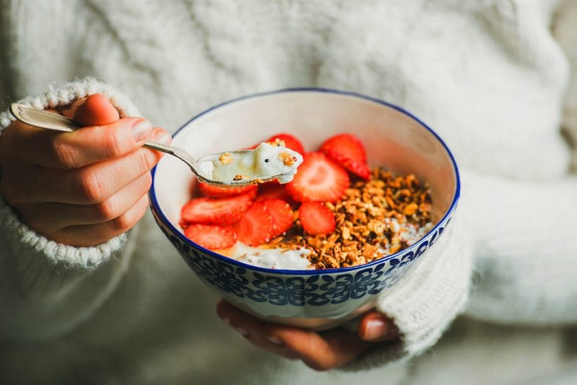 Woman holding a bowl of gluten free food for celiac disease diet