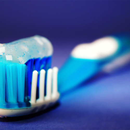 blue and white toothbrush with sparkling toothpaste on top