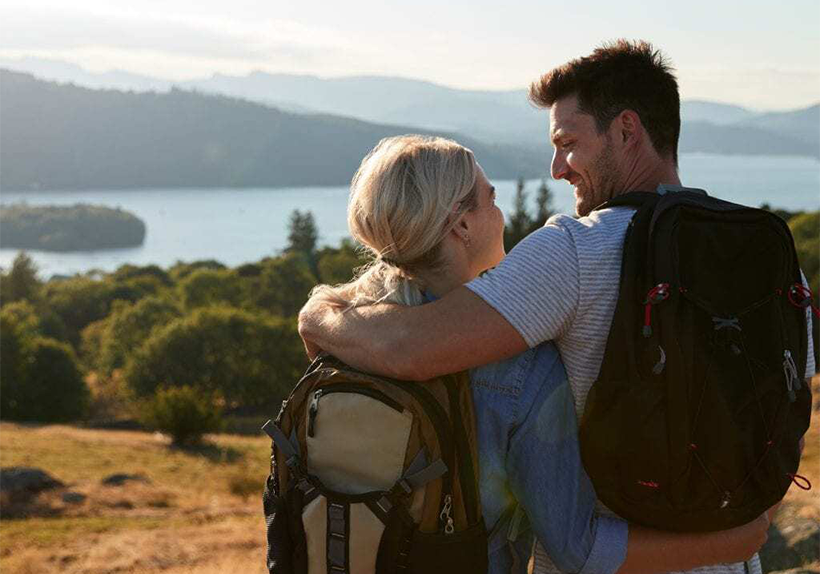 Dark haired man and blonde woman overlooking a lake in nature, wearing backpacks