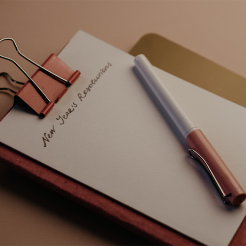 New Year's Resolutions list with red notebook with white paper and pen