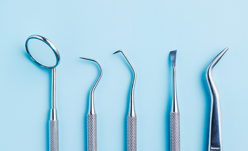 Five silver dentist tools with a blue background
