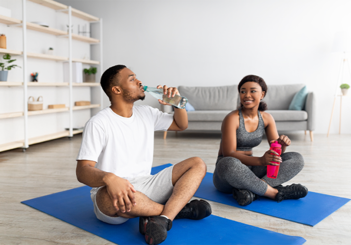 an African American male and female athlete drinking water staying hydrated