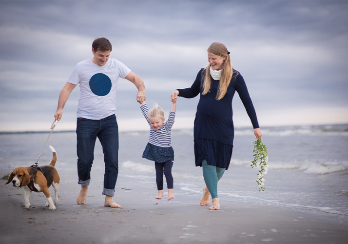 Dad and Mom swinging kid on the beach while walking a dog offsetting out-of-pocket costs