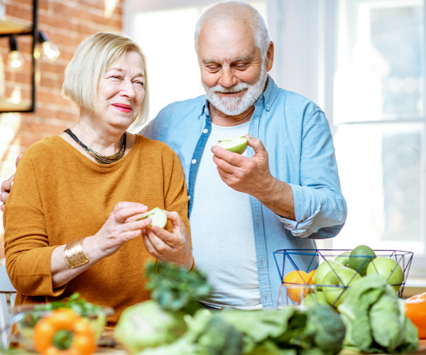 Woman in gold shirt and man in blue shirt standing in the kitchen looking at vegetables to increase immunity