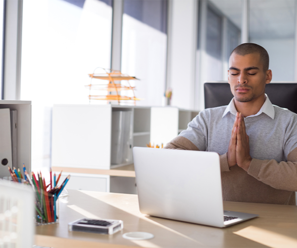 A man in a brown and gray shirt sitting at his desk at the office with eyes closed performing desk yoga with hands together at his chest.