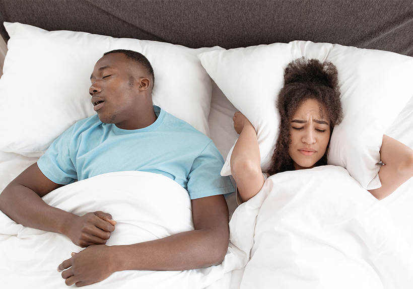 woman holds a pillow over her with husband snoring with sleep apnea