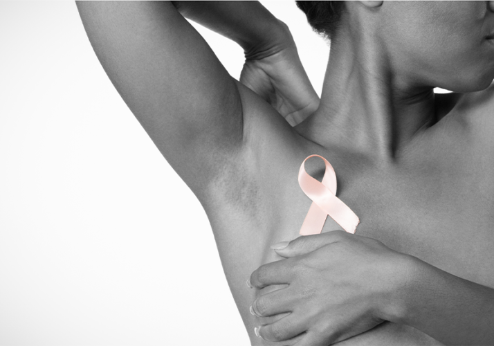 breast cancer awareness photo of a black woman covering herself and a light pink ribbon over her chest